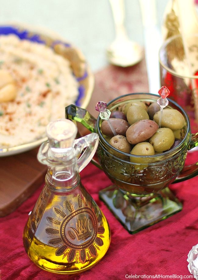 green dish of green olives and carafe of olive oil