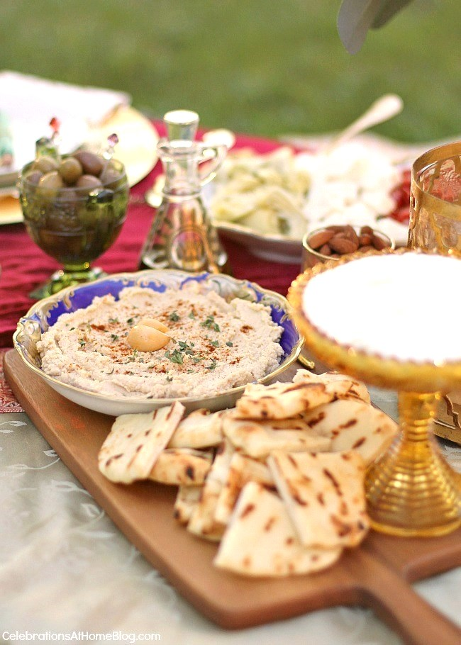 hummus in blue dish with pita bread on wooden board