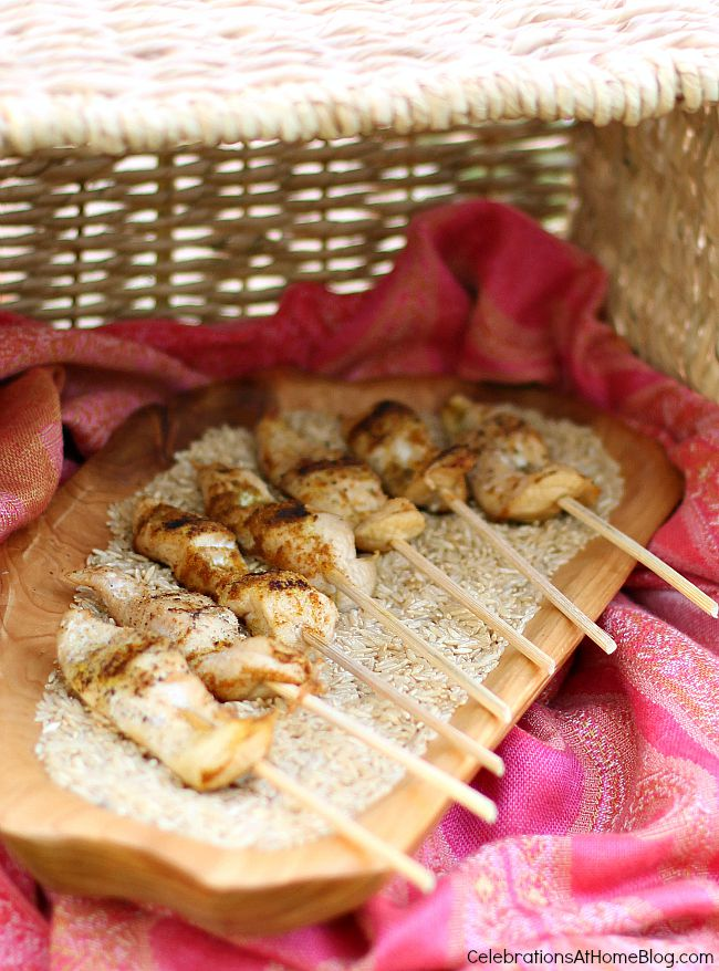 chicken skewers on a bed of dry rice in wood dish