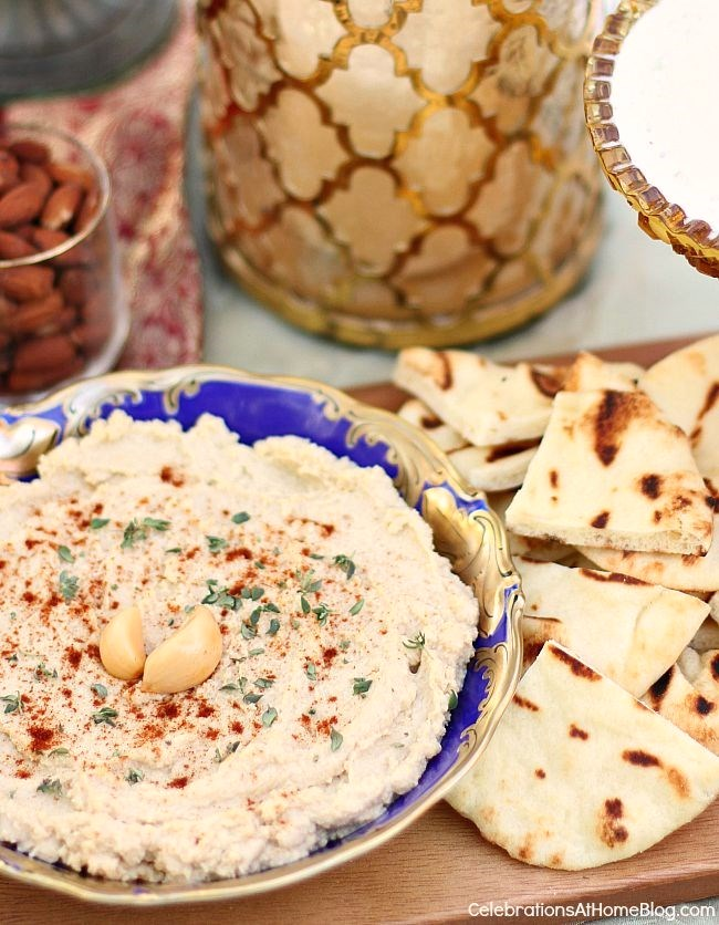 hummus topped with garlic cloves in blue dish