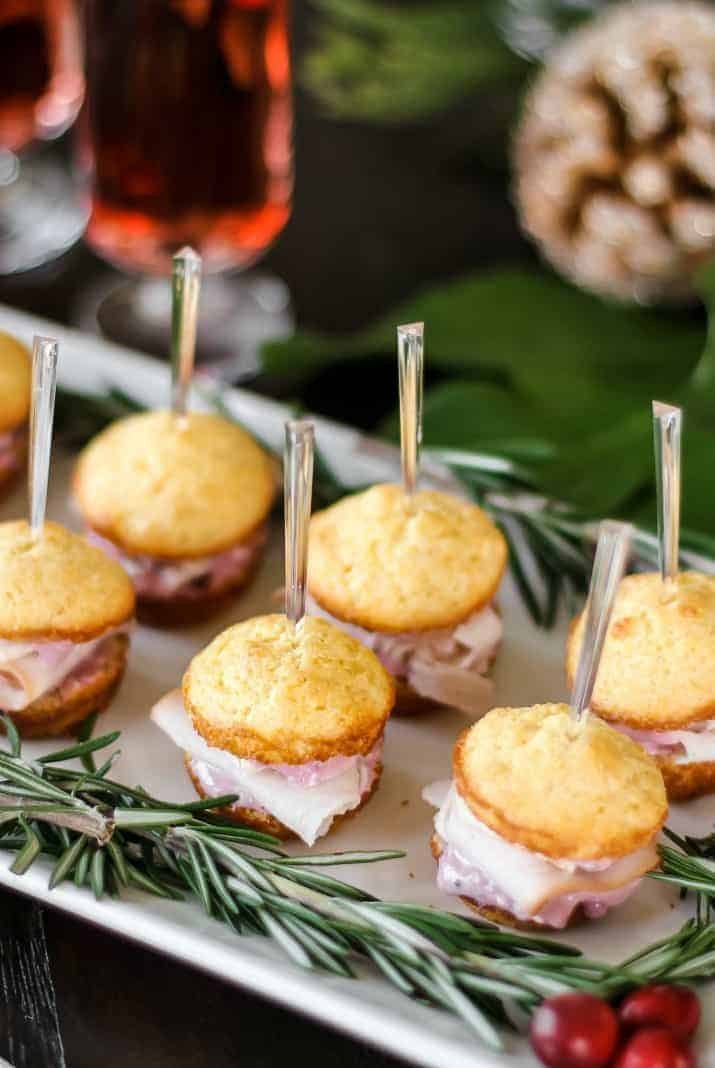 Christmas corn muffin appetizers on white platter with rosemary garland
