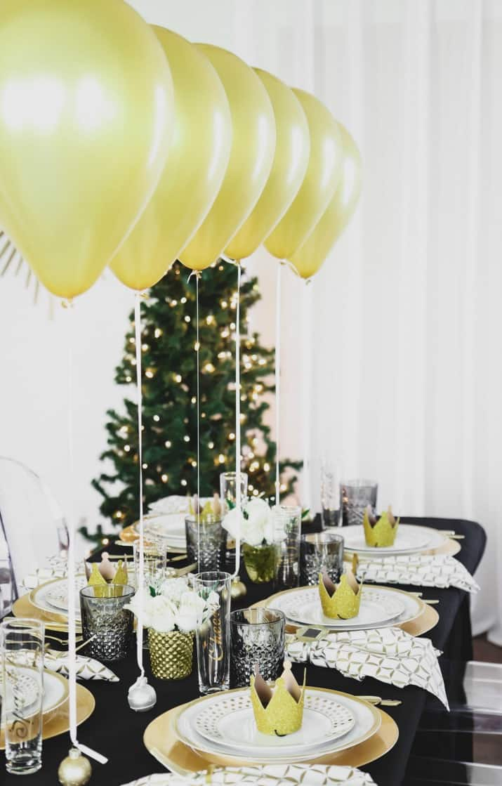 black and gold tablescape with balloons centerpiece