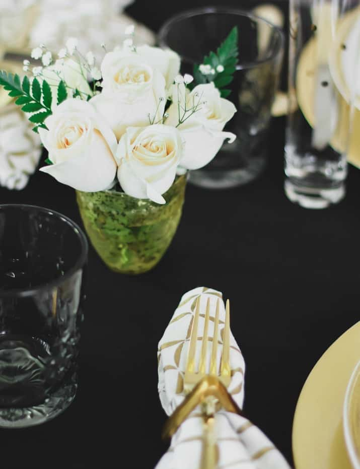 white roses on black and gold tablescape