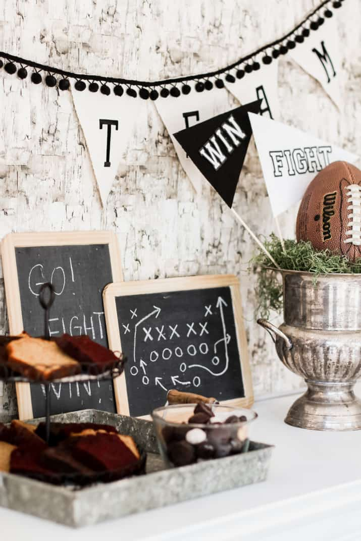 table with baked goods, chalkboards, and football trophy decor for a party