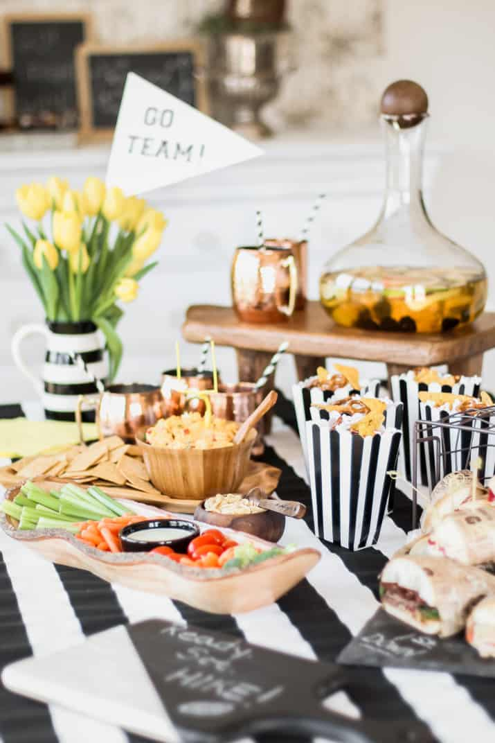 party table with black and white strip tablecloth, filled with party food.