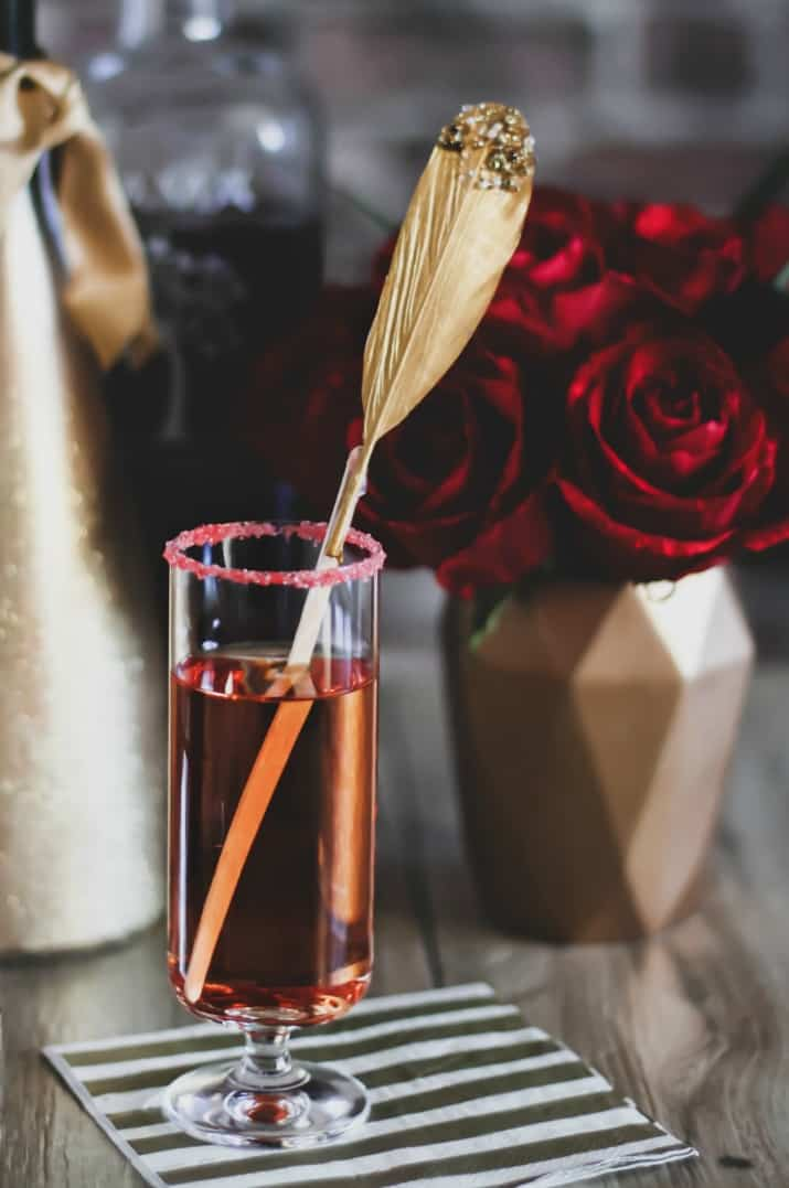 pomegranate sparkling cocktail with feather stir stick