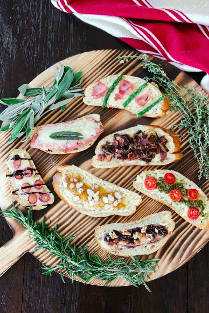grilled cheese tartines, 7 varieties on wooden board, overhead view