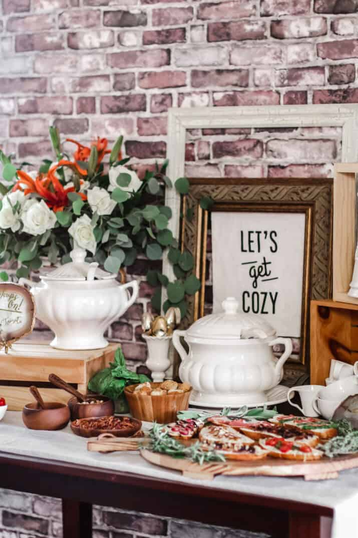 soup party buffet with flowers, toppings, soup tureens, and frames