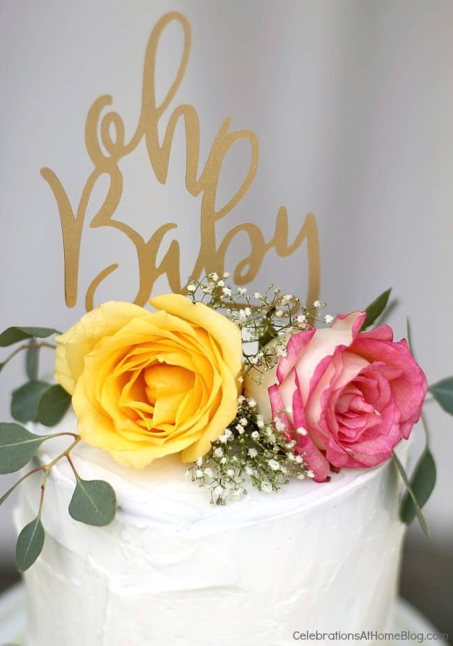 white cake topped with flowers and Oh Baby topper
