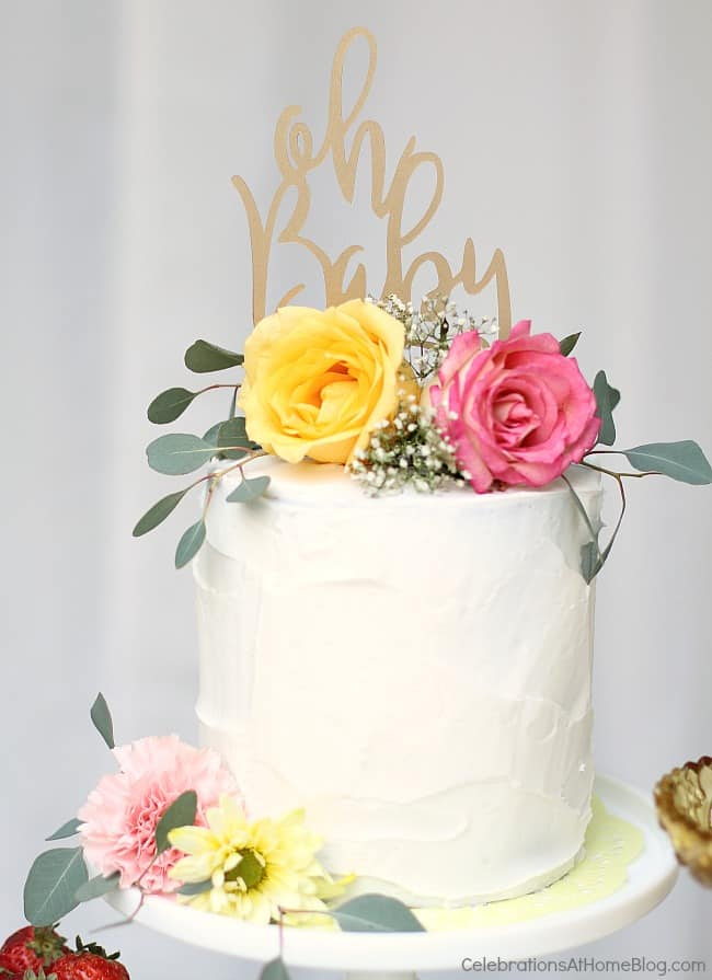 white cake with flowers on top and Oh Baby topper