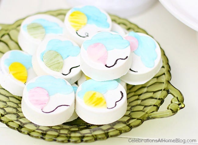 dipped Oreos decorated with balloon and cloud on green dish
