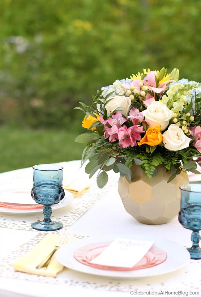 place setting with pink plate on top of white plate and floral centerpiece