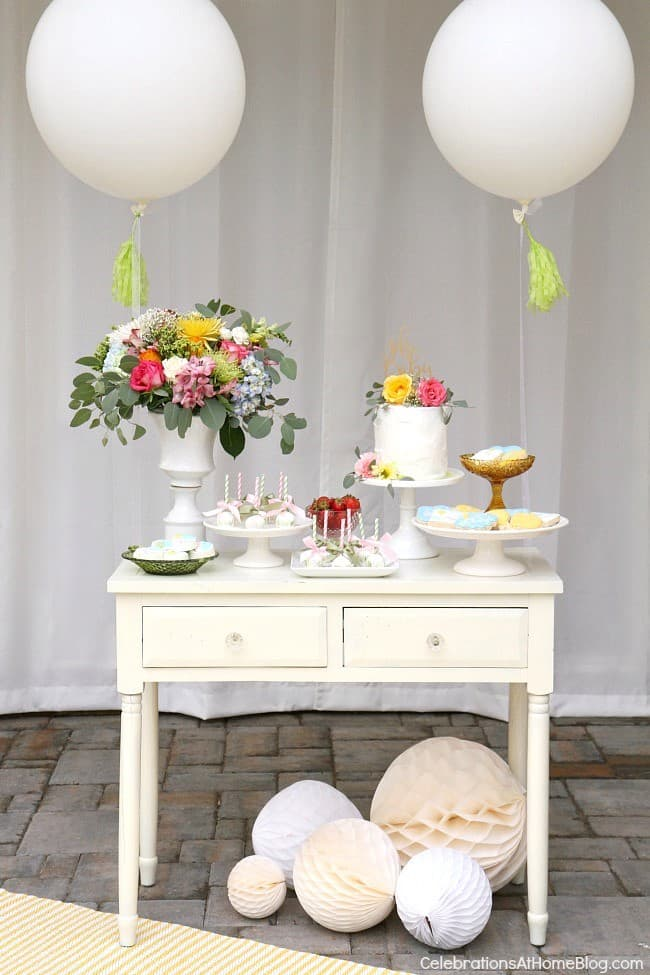 white dessert table with balloons flowers and cake