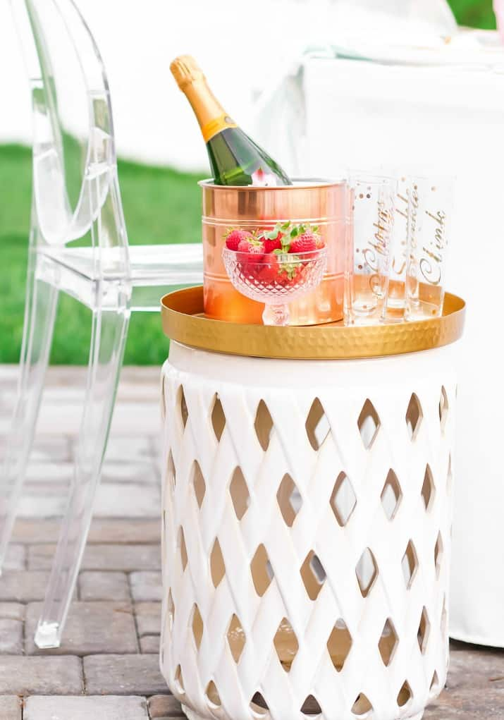 white table with champagne bucket and strawberries in pink dish