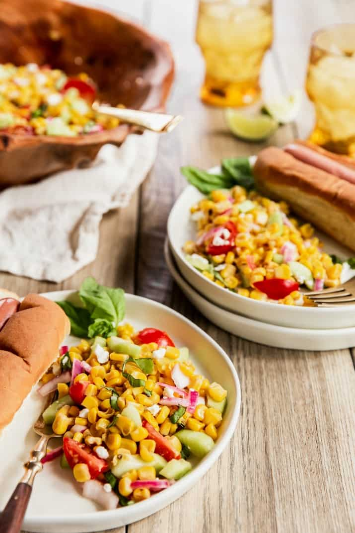 corn salad plated with hot dogs