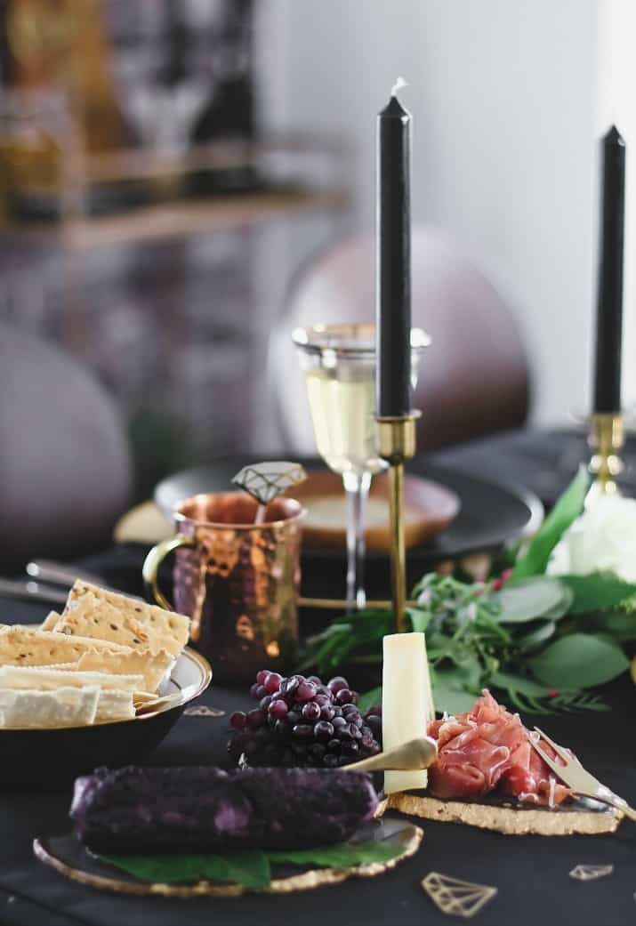Black & gold table setting with cheese and charcuterie