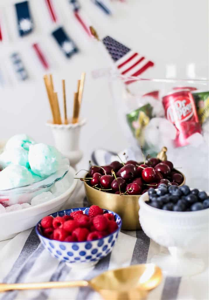 bowls of cherries, raspberries, and blueberries on white table
