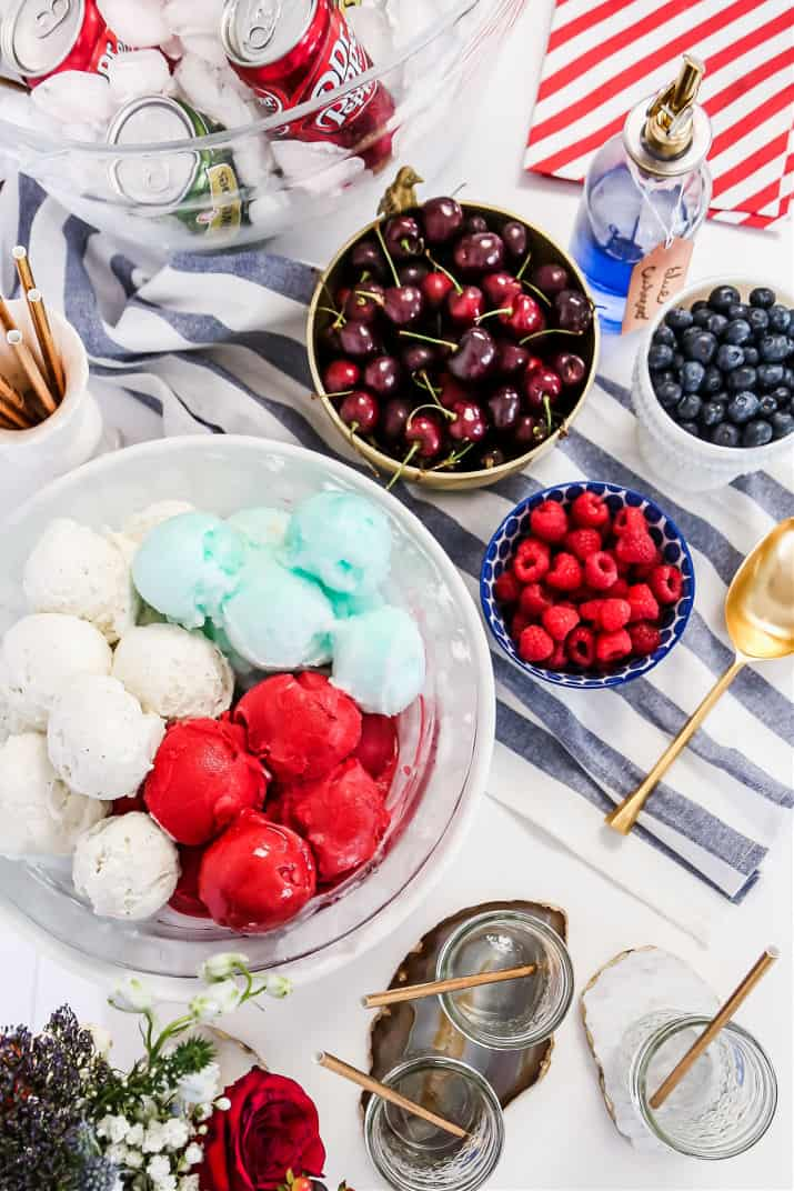 red, white, and blue ice cream scoops in a large bowl with fresh berry bowls, overhead view