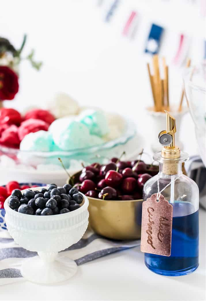 berries in bowls, and blue syrup in glass bottle