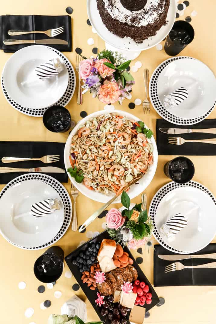 simple birthday celebration table, yellow table with black and white plate settings