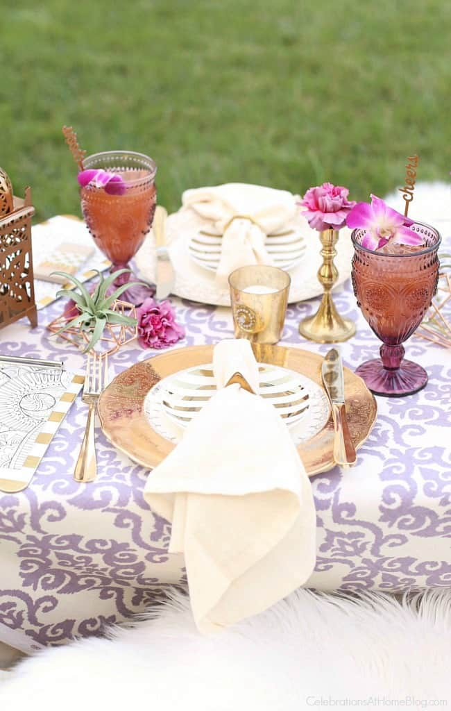 This Purple Celebration Tablescape with Floor Seating will inspire your next festive party. Gold place settings.