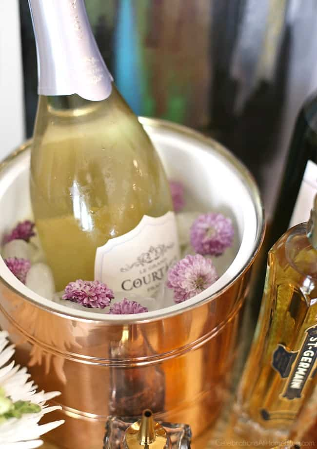 Bubbly bar with champagne on ice surrounded by flowers is perfect for brunch.