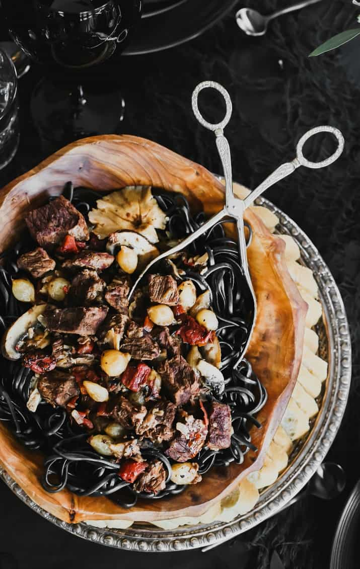 beef tips with mushrooms and onions over black noodles
