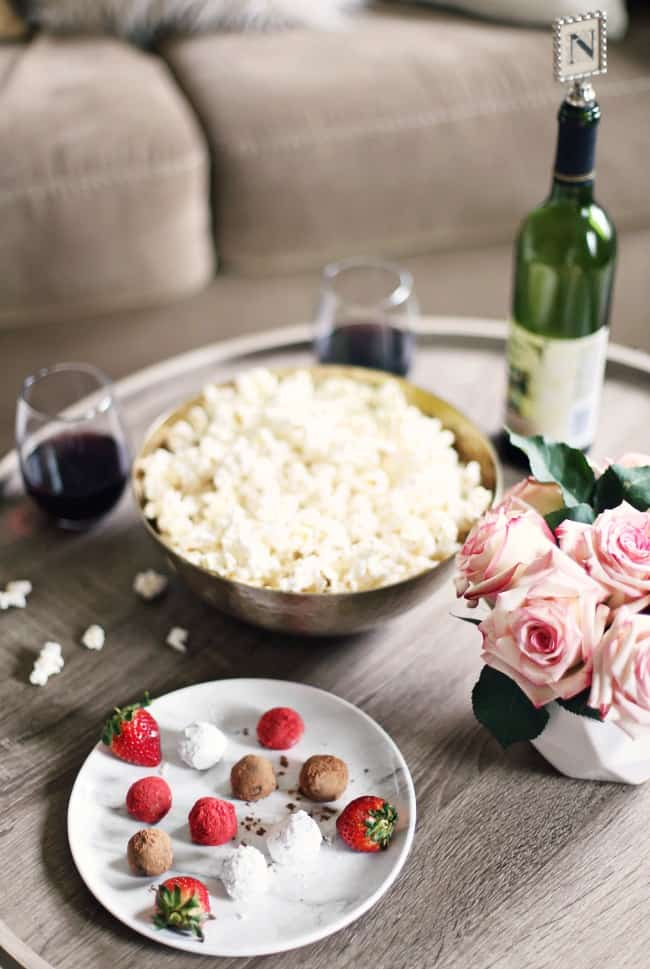 favorite romance movies for date night or girls night in, table with popcorn and wine