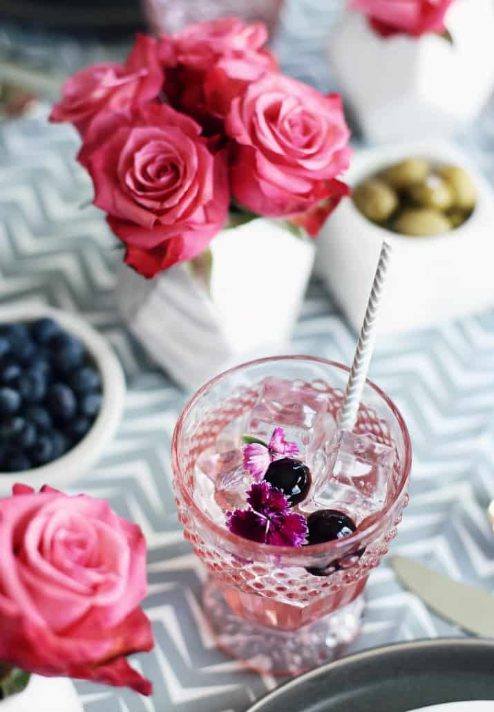 Pink & Gray Tablescape Celebration Dinner Party, pink glass with beverage garnished with cherries and flowers