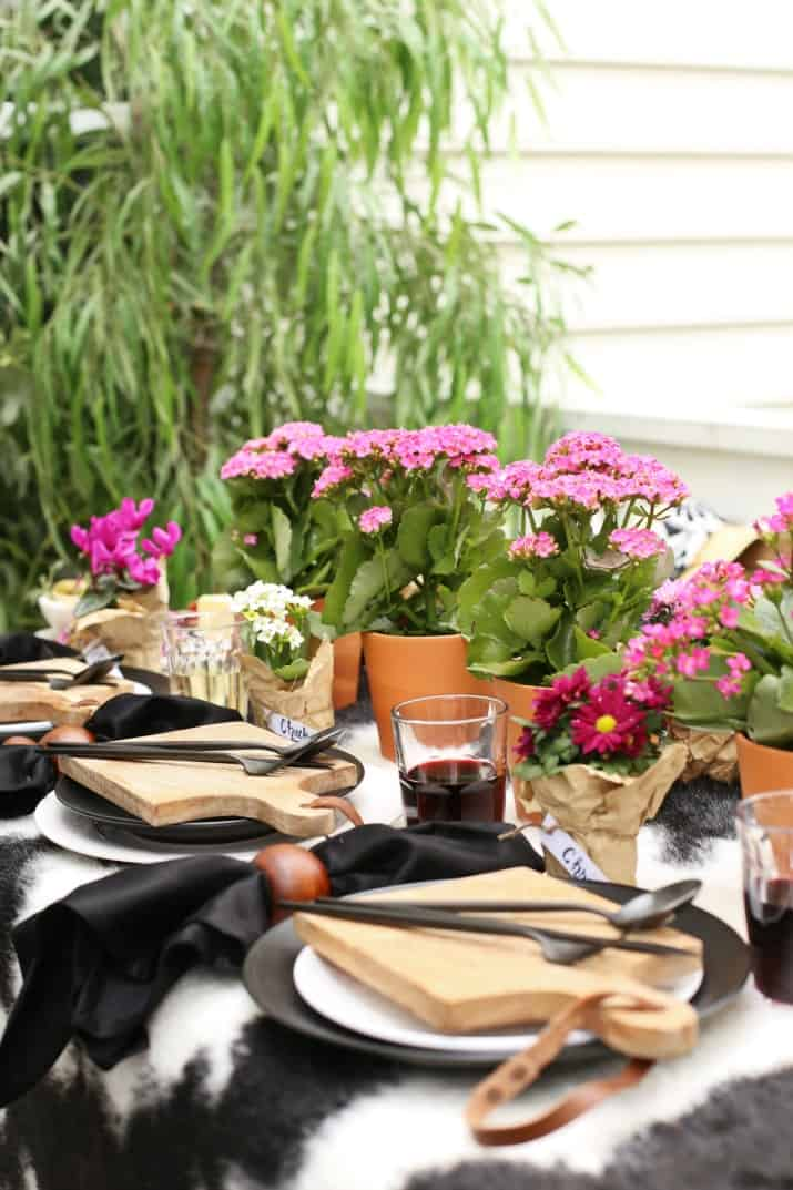 Outdoor Dinner Party Tablescape with Mini Cheese Boards and pink potted flowers centerpiece