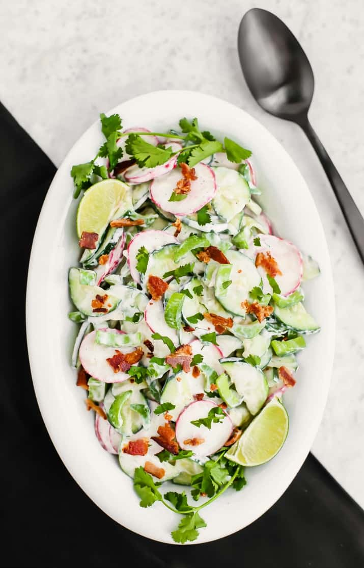 crunchy cucumber salad with bacon, in white dish overhead view