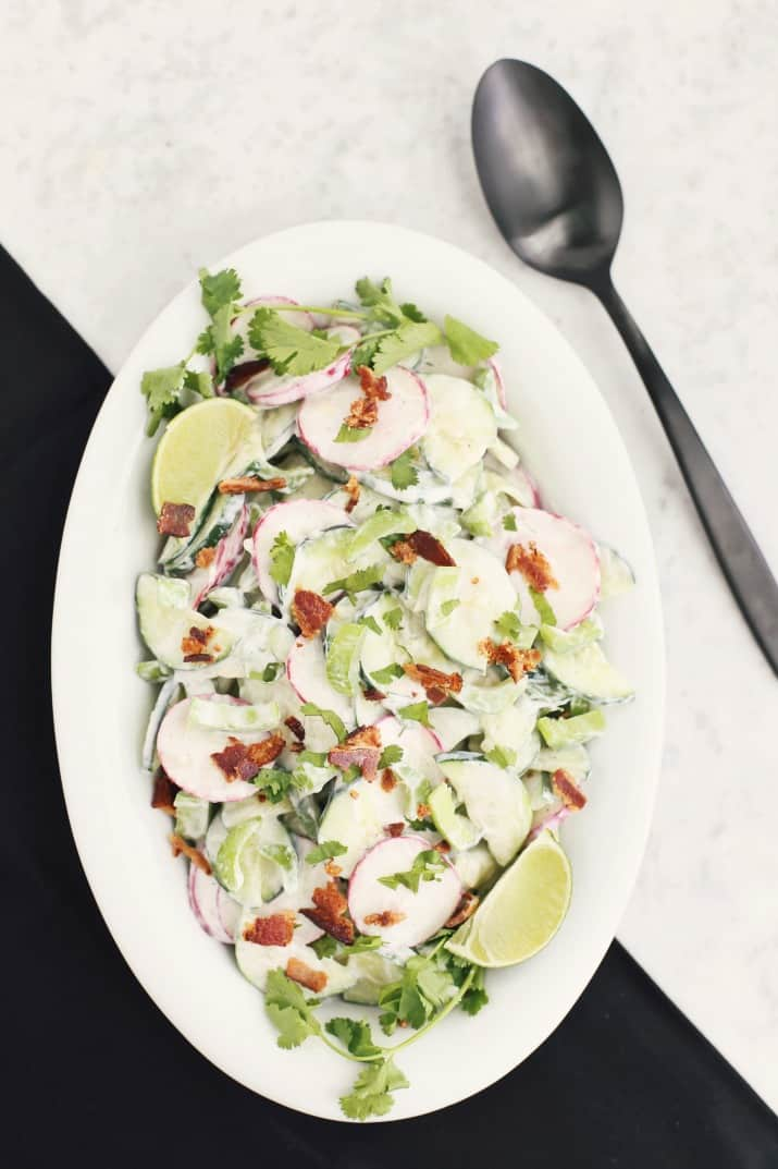 crunchy cucumber salad with bacon, in white dish