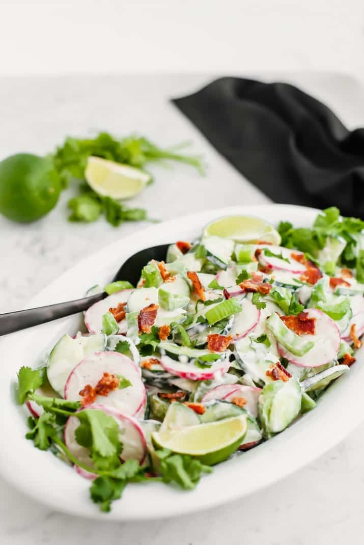crunchy cucumber salad with bacon, in white dish with black spoon