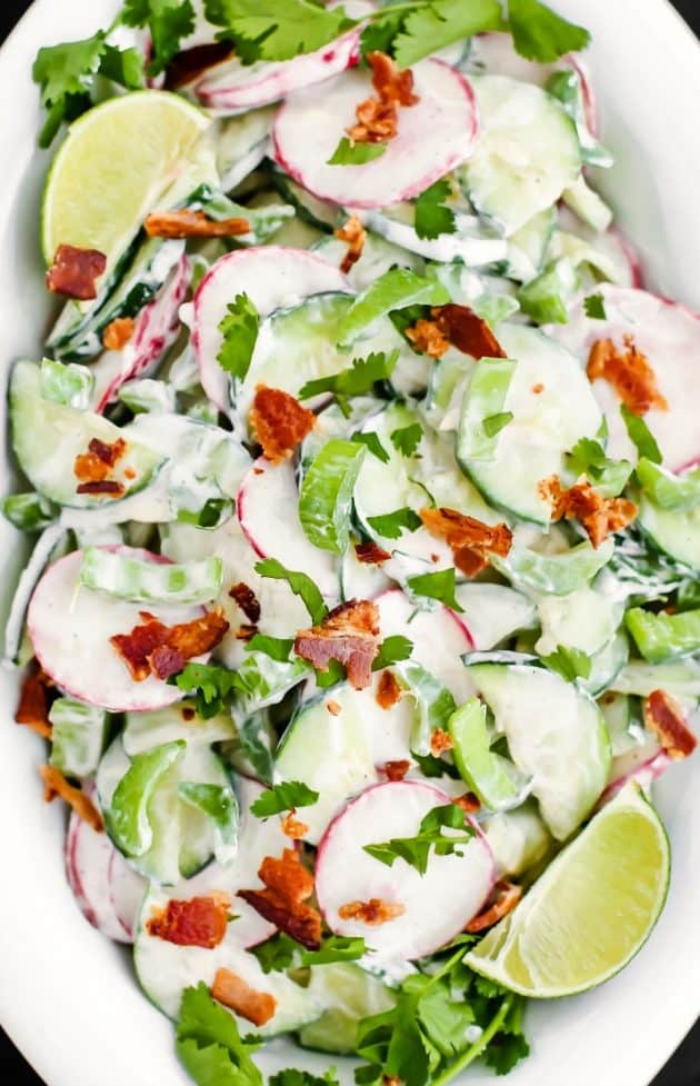 crunchy cucumber salad with bacon, in white dish overhead closeup view