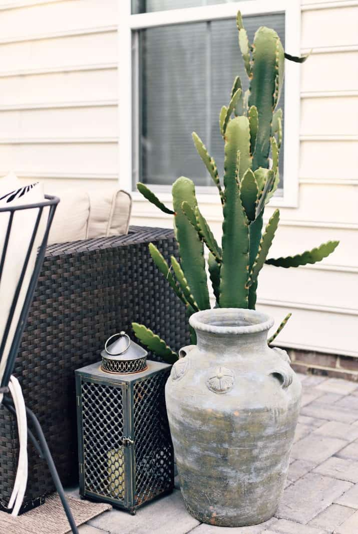 black & tan patio decor with greenery, lanterns, and pots
