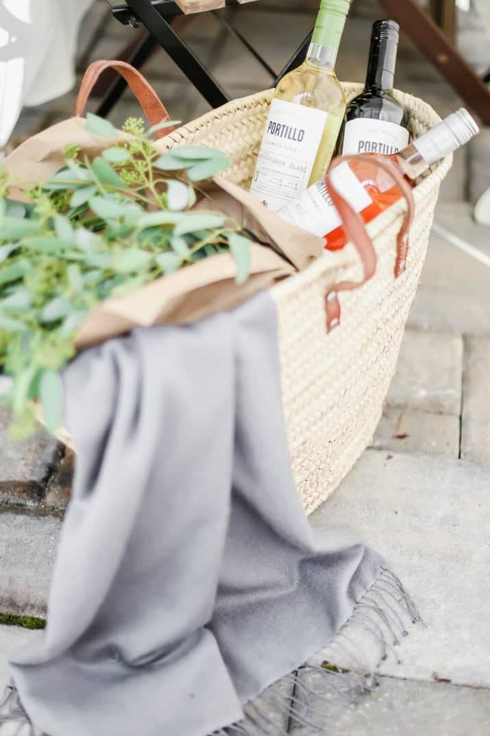 woven tote filled with wine and greenery
