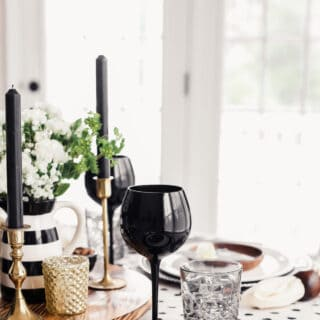 table setting with black charger, white plate, wood small plate
