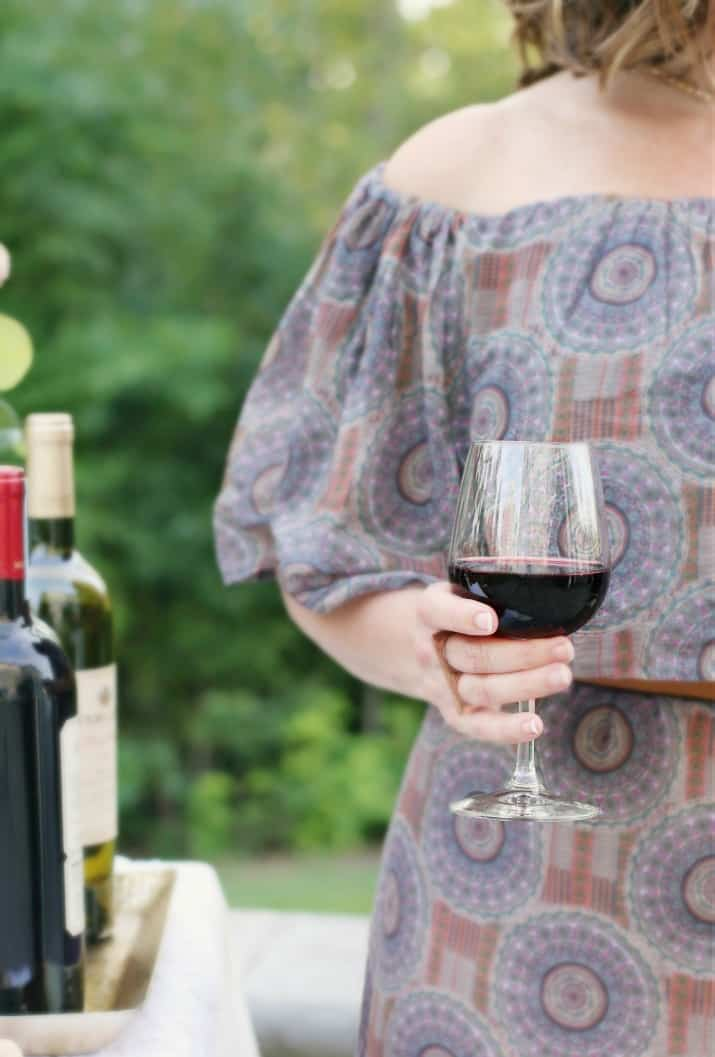 hostess holding glass of red wine