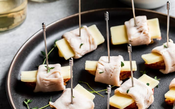 apples, cheese, and turkey bites on dark gray plate