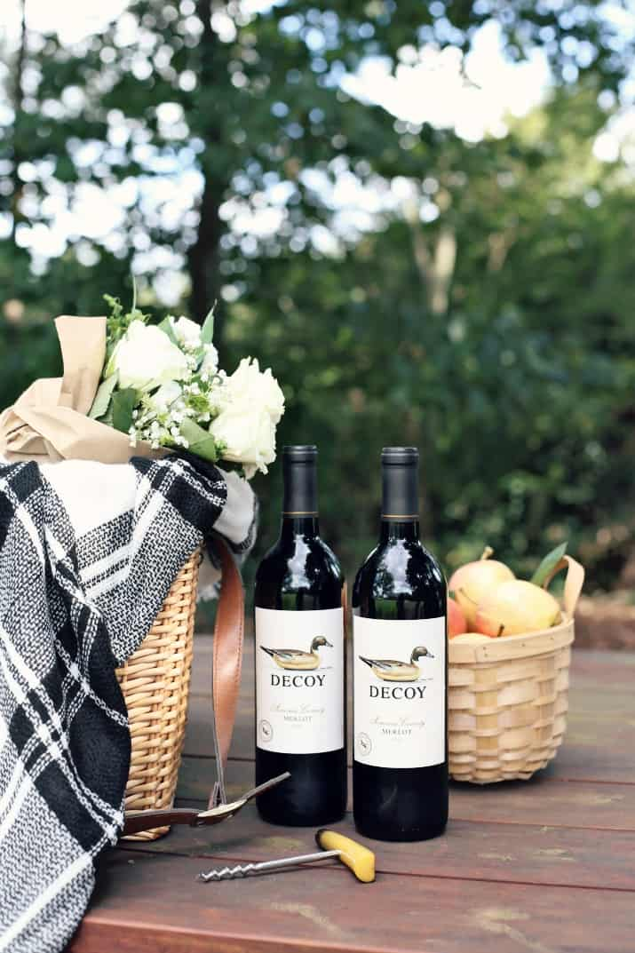 bottles of Merlot with picnic basket on table
