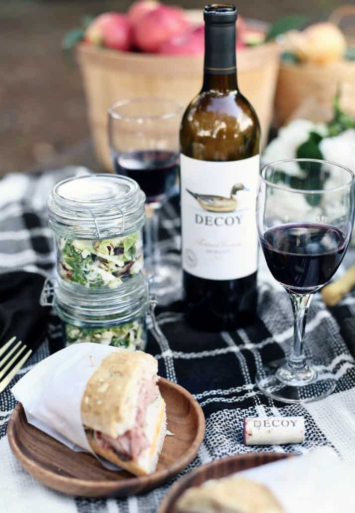 fall picnic with wine and sandwich and salad in a jar