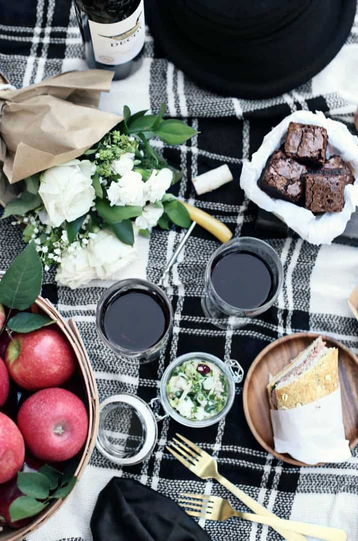 apple picking fall picnic with wine on black and white plaid blanket