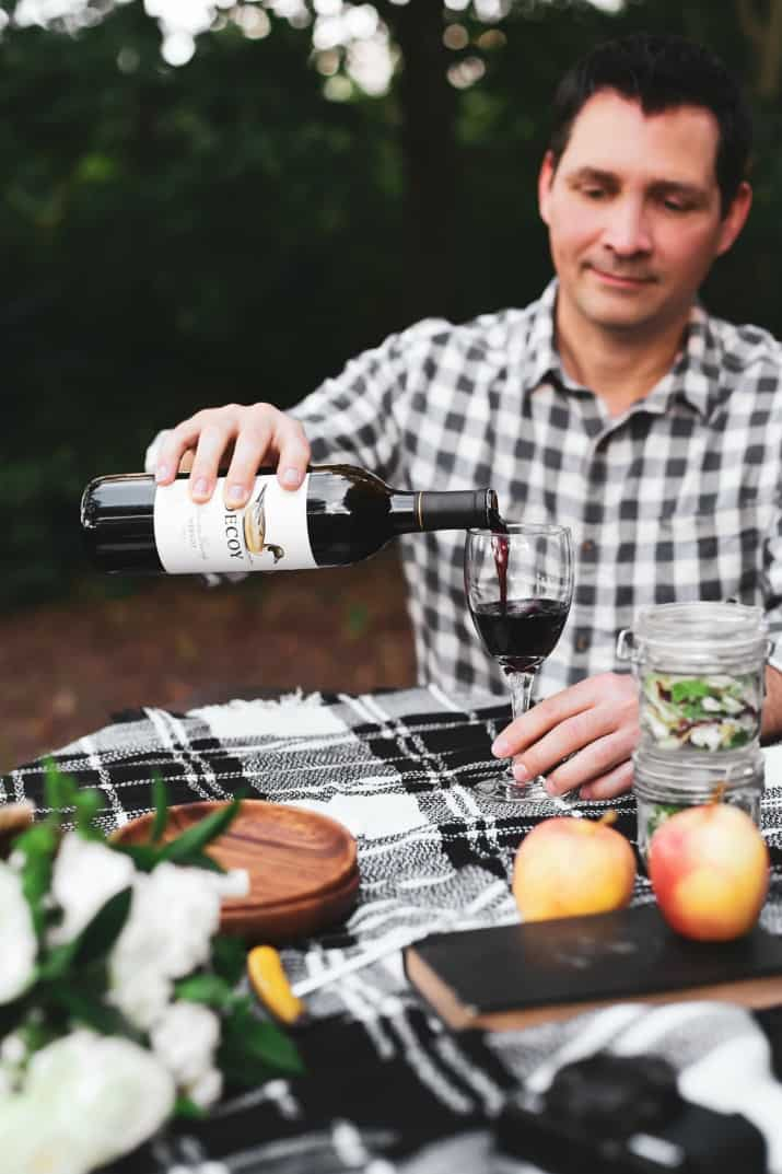 male pouring wine for picnic