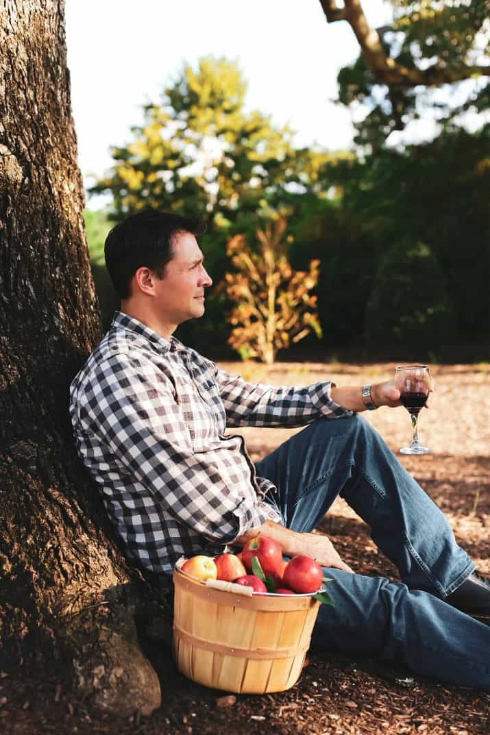 male sitting under tree with glass of wine