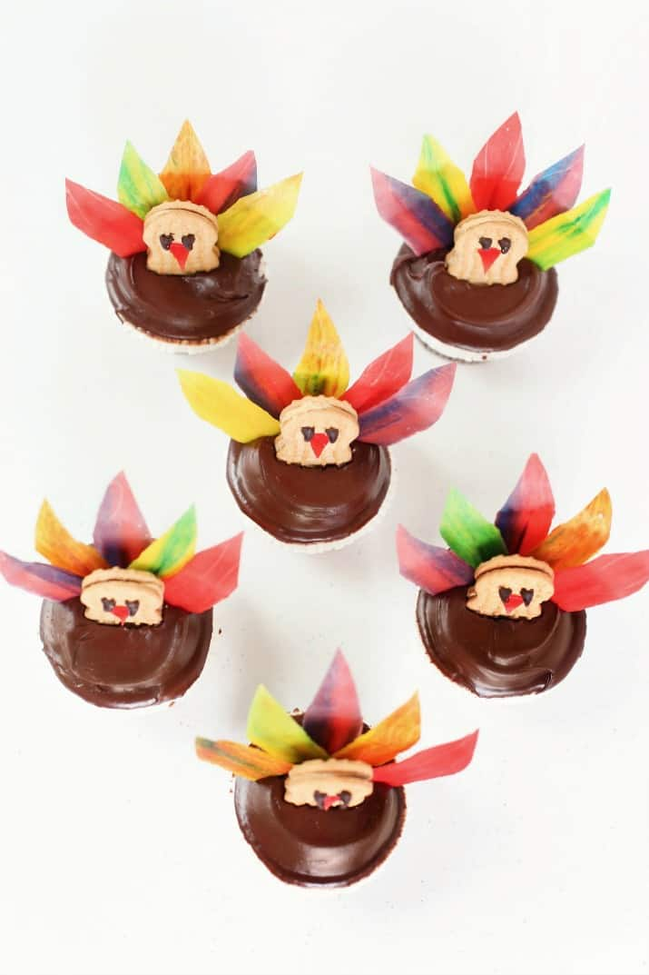 six diy Thanksgiving turkey cupcakes grouped together, top view