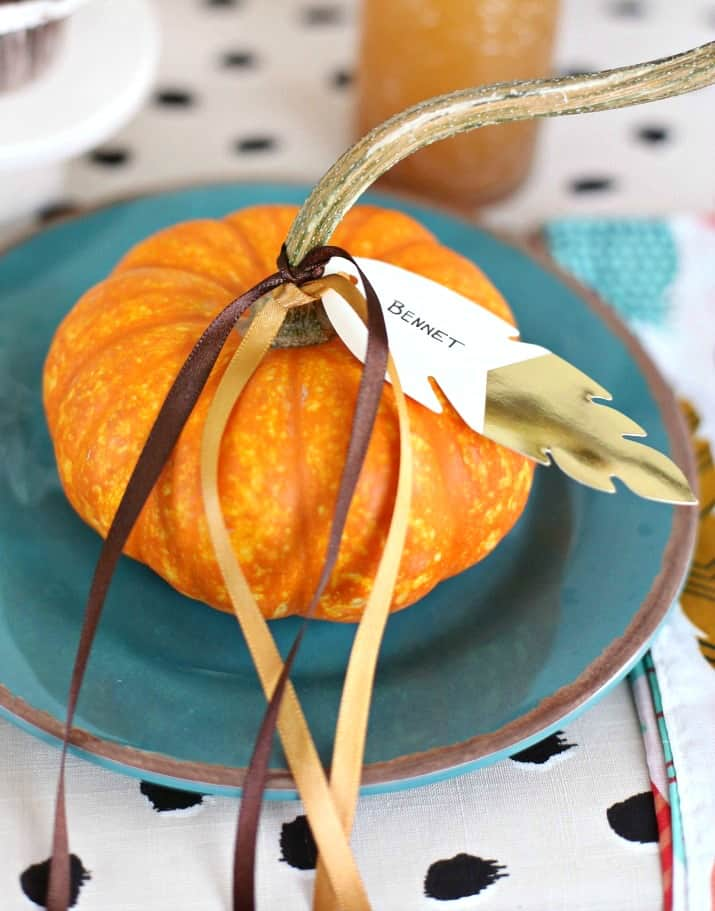 Thanksgiving kids table mini pumpkin with name tag tied on with ribbon