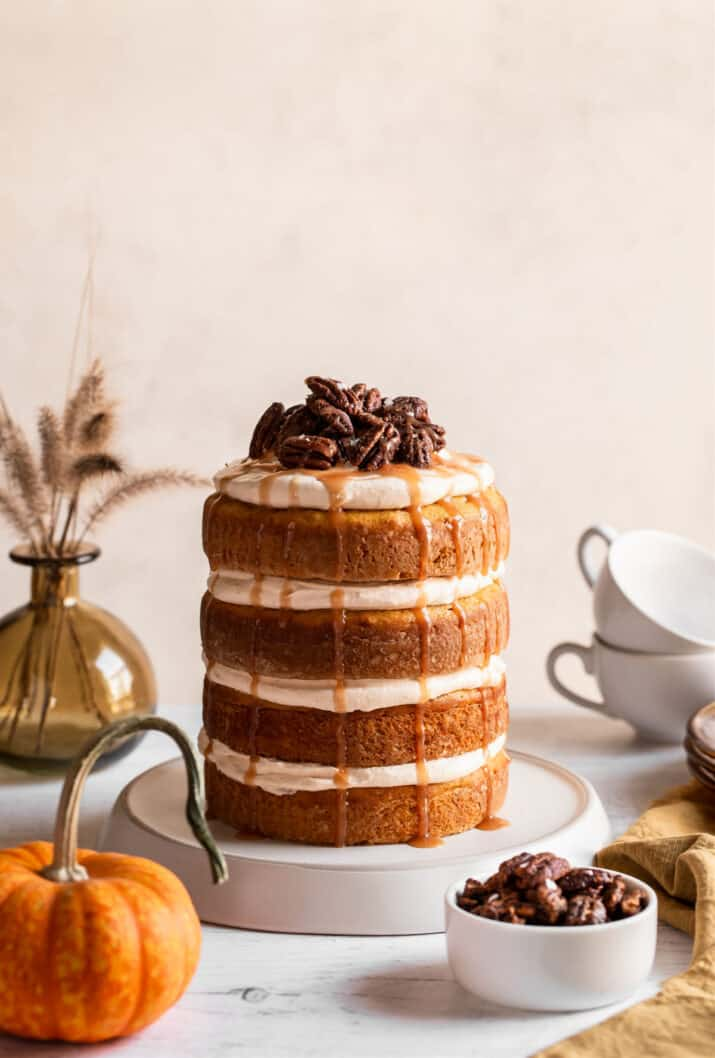 4 layer cake with creamy topping on table with mini pumpkin and candied pecans