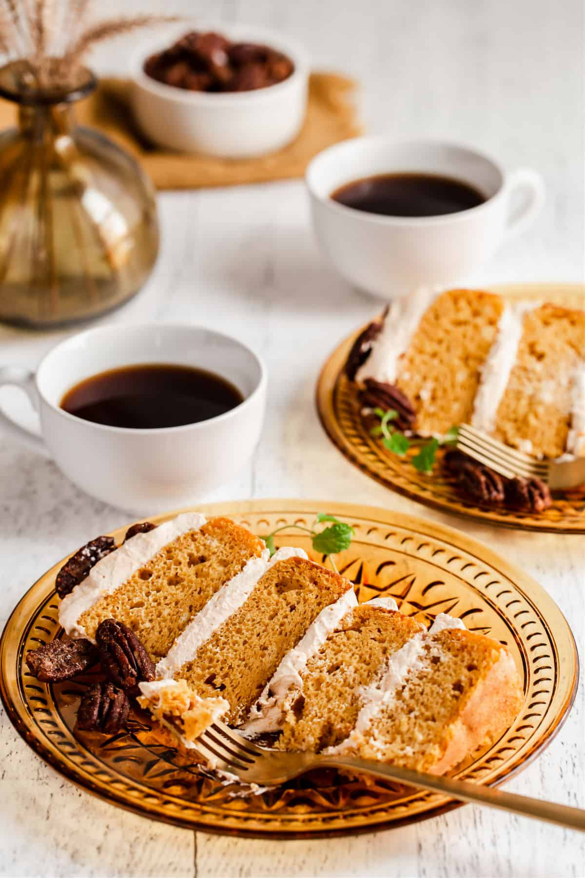 slice of 4 layer cake on golden plate with cup of coffee