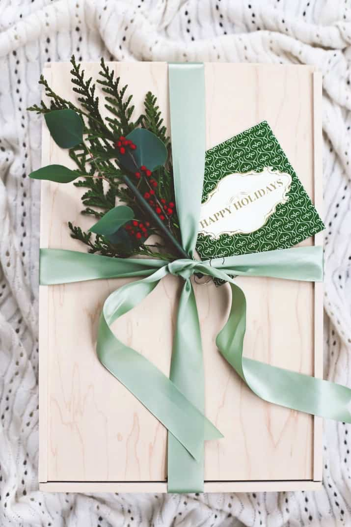 gift ideas, wooden box wrapped with green ribbon and greenery clippings