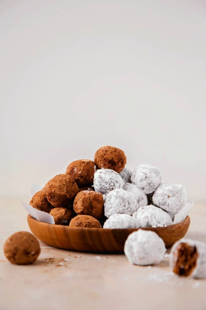 bourbon balls recipe, piled high on wood plate